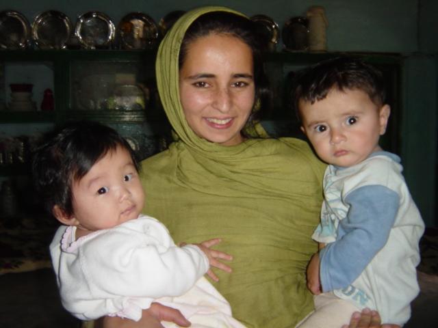 パキスタンの農村にて村の女性に抱っこされてご機嫌の長女